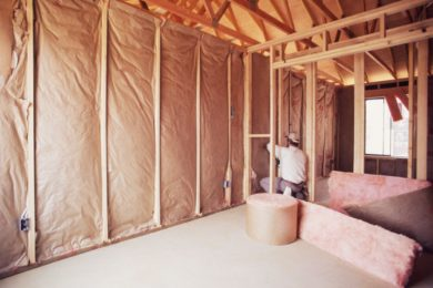 Attic Restoration: Cleanup & Repair Services - Columbus, Ohio. A man installs insulation inside a repaired attic.