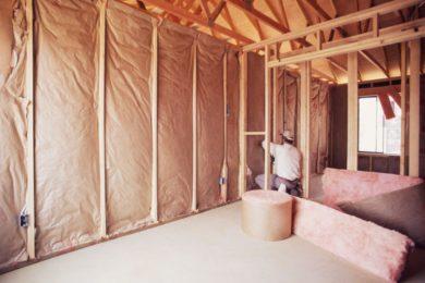 Attic Restoration: Cleanup & Repair Services - Columbus, Ohio. A man installs insulation inside a repaired attic.
